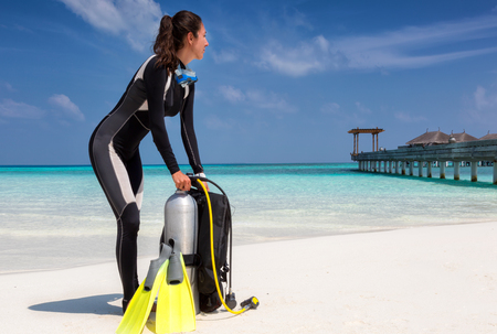 Female scuba diver with equipment on a tropical beach in the Maldives