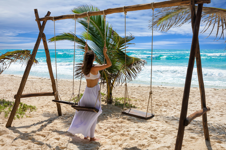 Woman in white dress on a swing at a caribbean beach with turquoise waters, Tulum, Mexico