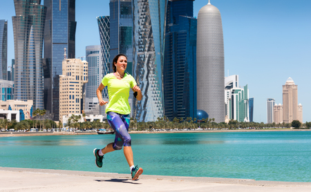 Sportive female runner in front of the skyline of Doha, Qatar