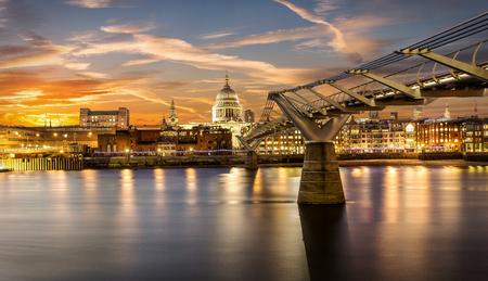 Millennium Bridge and St. Pauls church in London during sunset