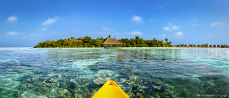 View from a canoe over coral gardens and pristine waters to an Maldivian island Stock Photo