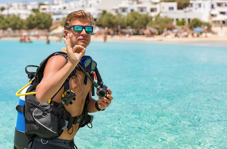 Male scuba diver gives the OK sign in front of turquoise waters Stock Photo