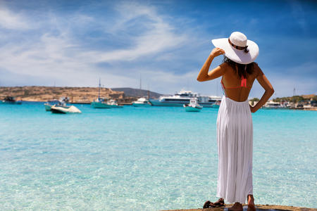 Elegant woman in white dress enjoys the view to the clear waters of the Koufonisia Islands, Greece
