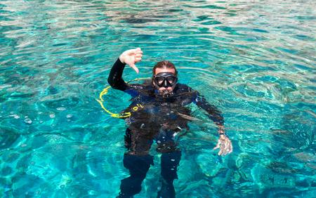 Male scuba diver gives dive down sign in mediterranean sea