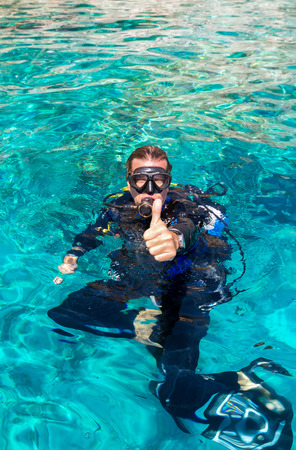 Male scuba diver in water shows the thumbs up sign