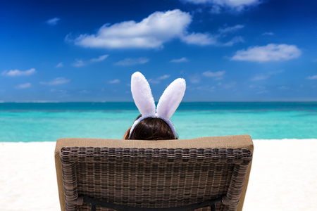 Easter travel concept: Woman with bunny ears on a tropical beach Stock Photo