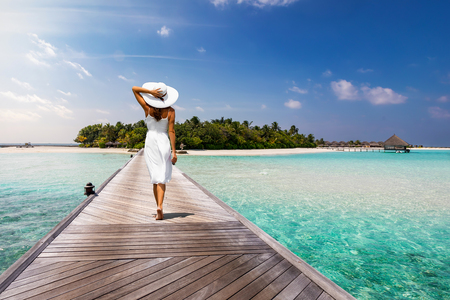 Attractive woman in white walks over a wooden jetty towards a tropical island