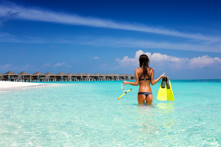 Attractive vacation woman stands with snorkeling gear in the tropical sea of the Maldives