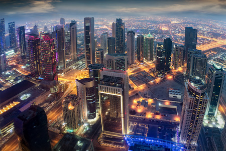Aerial view to the illuminated city center of Doha, Qatar during evening time