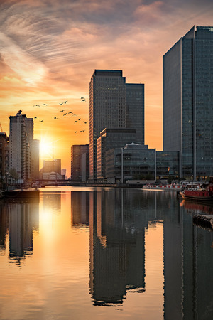 The financial district Canary Wharf in London during sunset with reflections in the water Stock Photo