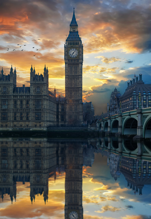 Cloudy sunset behind the Big Ben clocktower by the Thames river in London, United Kingdom