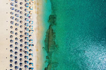 Aerial top view of Kalafatis beach on Mykonos island, Greece, with emerald sea, umbrellas, sunchairs and fine sand