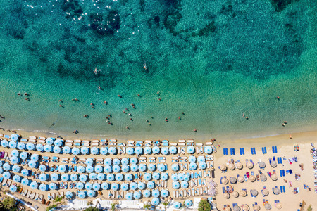 Aerial top down view to the famous beach of Psarou on Mykonos island with dense umbrellas and sunbeds, Cyclades, Greece