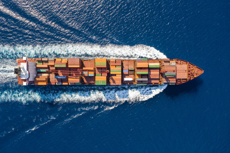 Aerial top down view of a large container ship in motion over blue, open ocean; global transport of cargo on sea Фото со стока
