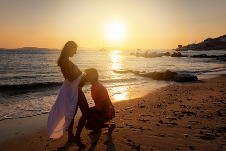Man kisses the belly of his pregnant wife on a beach during a romantic sunset Фото со стока