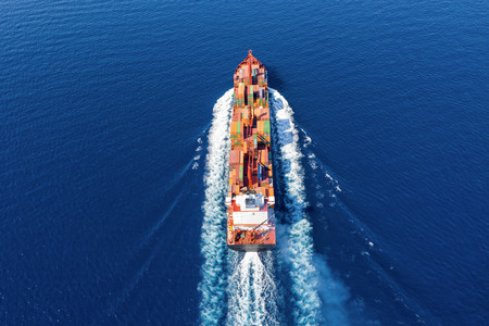Aerial view of a container ship in motion over the open ocean; concept of global transport of cargo on sea