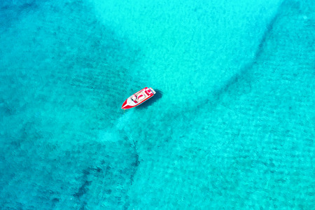 Aerial view of a moored motorboat over sparkling, turquoise sea on Mykonos island, Greece Фото со стока