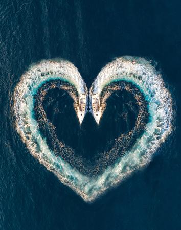 Dos barcos forman un corazón en la superficie del océano; vista aérea desde arriba Foto de archivo