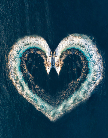 Two boats form a shape of a heart on the ocean surface; aerial top down view Фото со стока - 110954232