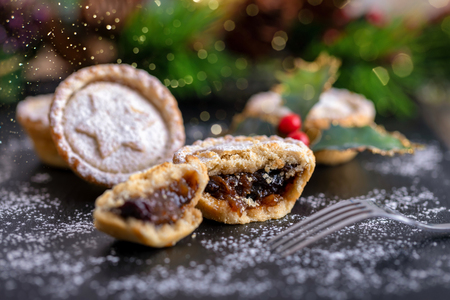 Classic British Mince Pies for the festive Christmas season on a black slate plate Stock Photo