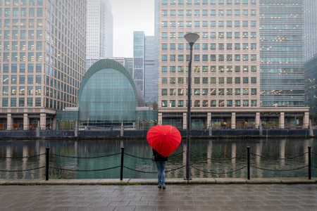 Woman with red, heart shaped umbrella stands in London Canary Wharf on a rainy autmun day