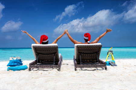 Winter vacation concept: happy couple wearing santa hats in sun chairs on a tropical beach during Christmas time