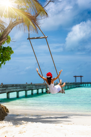 Woman white dress and red santa hat enjoys her winter vacations on a swing at a tropical beach Reklamní fotografie