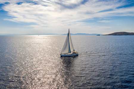 Aerial view of a sailingboat on the blue, mediterranean sea against the sparkling sunlight