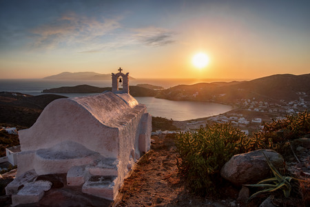 Summer sunset over the Aegean Sea with a Greek church in front seen on the island of Ios, Cyclades, Greece