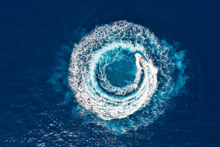 Motorboat forms a circle of waves and bubbles with its engines over the blue sea Фото со стока