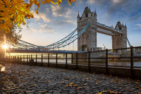 London in autumn time: golden sunrise behind the Tower Bridge with autumn leafs, United Kingdom