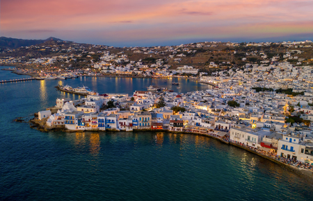 Aerial view of the town of Mykonos after sunset with illuminated city lights and orange sky, Cyclades, Greece Фото со стока