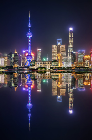 The colorful illuminated urban skyline of Shanghai during night time with reflections in the Huangpu river, China