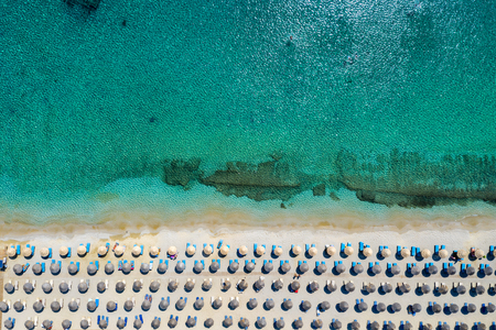 Aerial topdown view to the beach of Kalafatis with symmetrical lined up umbrellas and sunbeds, Mykonos, Cyclades, Greece