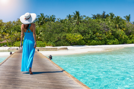 Attractive woman in a blue dress walks towards a tropical paradise island with turquoise waters and green palm trees