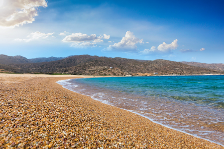 Fine pebble sand and turquoise waters at Kalamos beach on the island of Ios, Cyclades, Greece Фото со стока