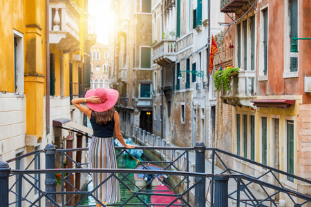 Traveller woman with red hat stands on a bridge and enjoys the view to a canal with passing by gondola in Venice, Italy Фото со стока