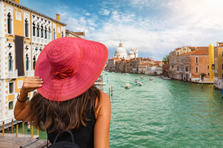 Tourist woman with red sunhat overlooks the Canal Grande in Venice on a sunny summer day, Italy