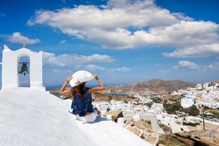 Traveller woman sits next to a orthodox, Greek church above the Chora of Ios and enjoys the scenery, Cyclades, Greece