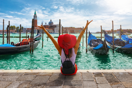 Happy traveller woman sits in front of the traditional gondolas of St. Marks Square in Venice, Italy