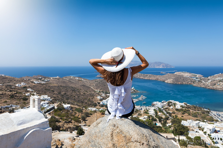 Elegant woman sits on a rock high over the village of Ios island and enjoys the view, Cyclades, Greece Фото со стока