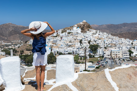 Attractive, female tourist enjoys the view to the white town of the island of Ios, called Chora, on a suny summer day, Cyclades, Greece