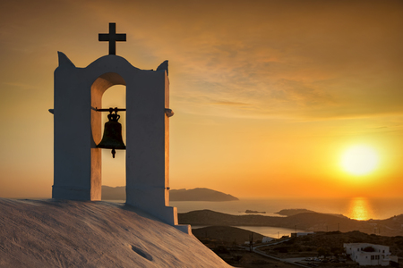 Romantic sunset seen from an old white orthodox church overlooking the Aegean sea, in Cyclades islands, Greece Фото со стока