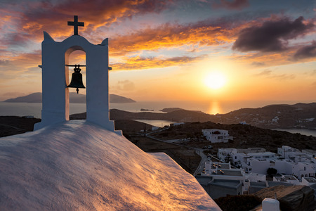 Sunset over the Aegean Sea and the Cyclades island with a Greek orthodox church in front, Greece
