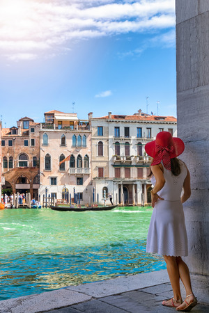 Female traveller woman enjoys the view to the architecture of the Canal Grande in Venice, Italy, on a sunny summer day Фото со стока