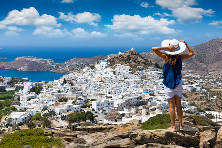 Traveller woman with white hat overlooks the town of the island Ios on the Cyclades in Greece during summer time Фото со стока