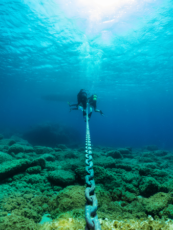 Group of Scuba divers peprforms a safety stop on an anker chain