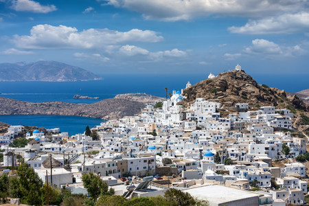Panoramic view to the town of Ios island, Chora, and the beneath lying port on a sunny summer day, Cyclades, Greece Фото со стока