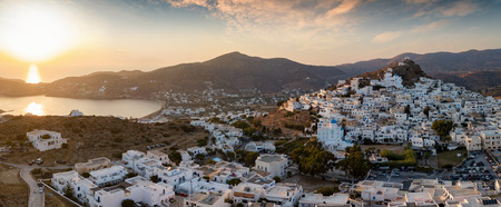 Panoramic view over the town and harbour of Ios island on the Cyclades in Greece during sunset time