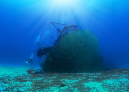 Ein versunkenes Schiffswrack im Mittelmeer mit einem Taucher, Griechenland